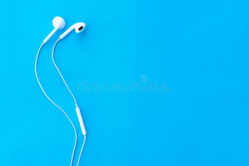 白色耳机顶视图可爱的特写镜头在蓝色淡色背景的 淡色概念 最小的概念 复制空间 音乐是 库存图片