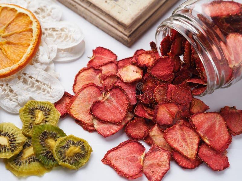 白色背景、顶视图上自制的干橙、草莓和猕猴桃片 免版税库存照片