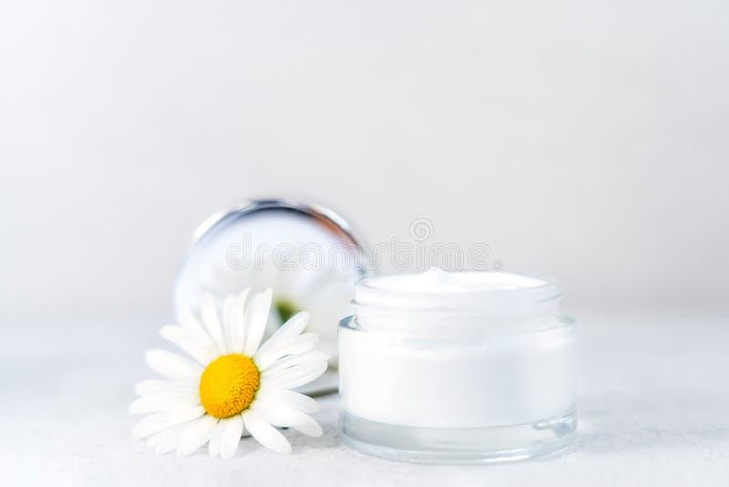 白色背景下开有玻璃容器和鲜花的甘菊草化妆品 天然有机 免版税库存照片
