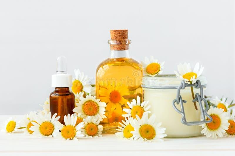 白色背景下甘菊花和精油和提取物的化妆品瓶 复制空间 免版税库存图片