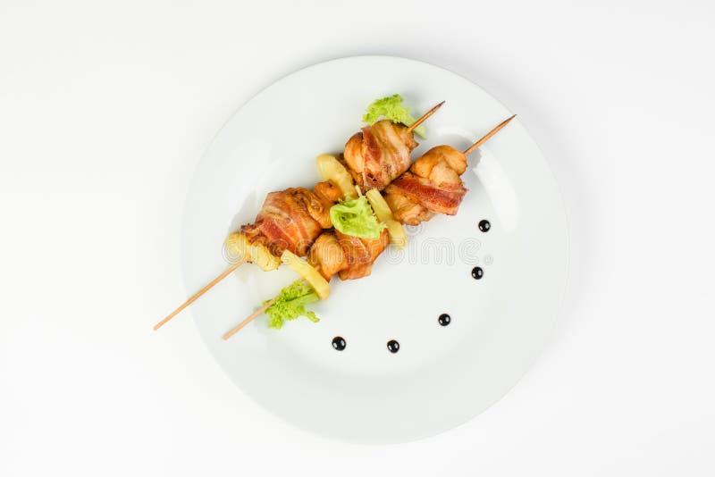 白色背景中圆形白盘上的鸡肉、菠萝和培根的烤肉串 免版税库存照片