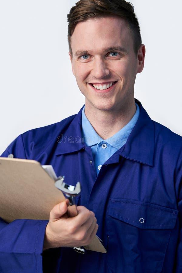 白色背景中带夹板扳手的男工程师摄影棚 免版税库存图片