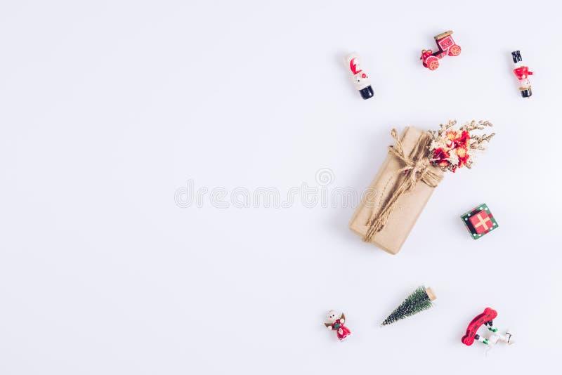 白色背景中带玩具装饰的手工圣诞礼盒,并有复制空间供您阅读 平面平顶视图 库存照片
