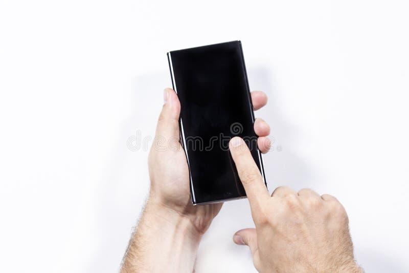 白色背景中手持智能手机的男子,手特写 库存图片