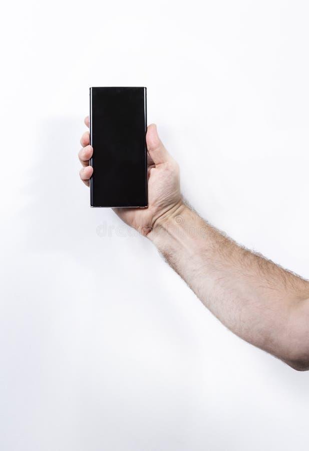 白色背景中手持智能手机的男子,手特写 免版税库存照片