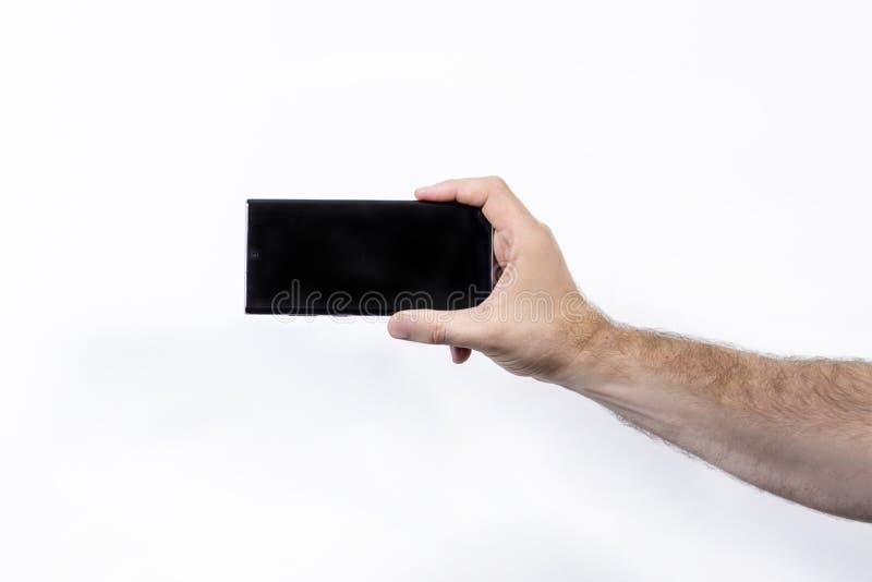 白色背景中手持智能手机的男子,手特写 免版税库存图片