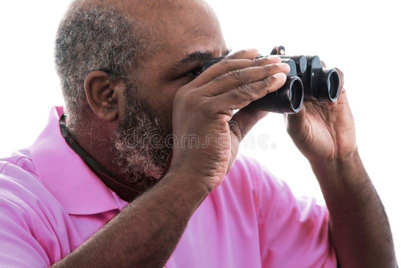 白色背景中透过双筒望远镜的非洲裔美国人 免版税图库摄影