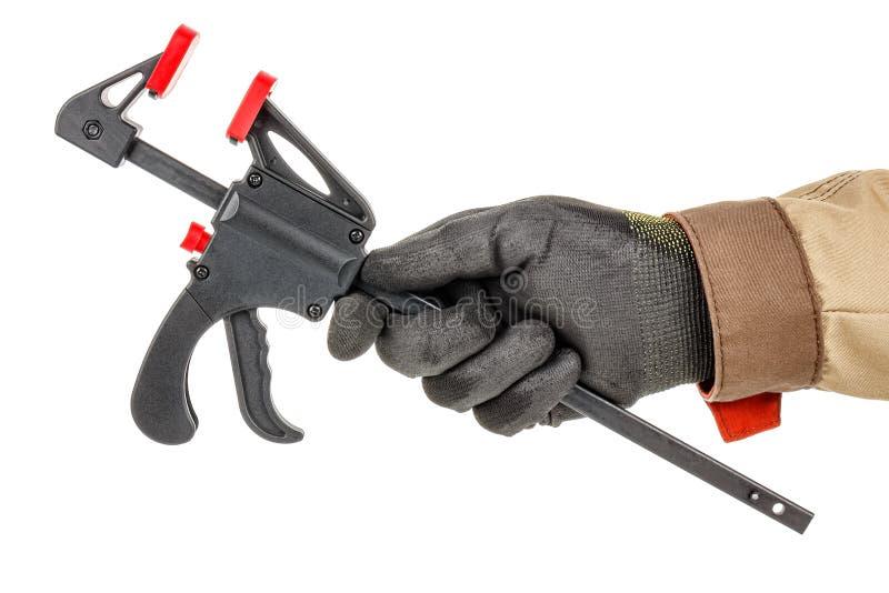 白色背景中黑色防护手套和棕色均匀的工人手快速释放夹具 免版税图库摄影