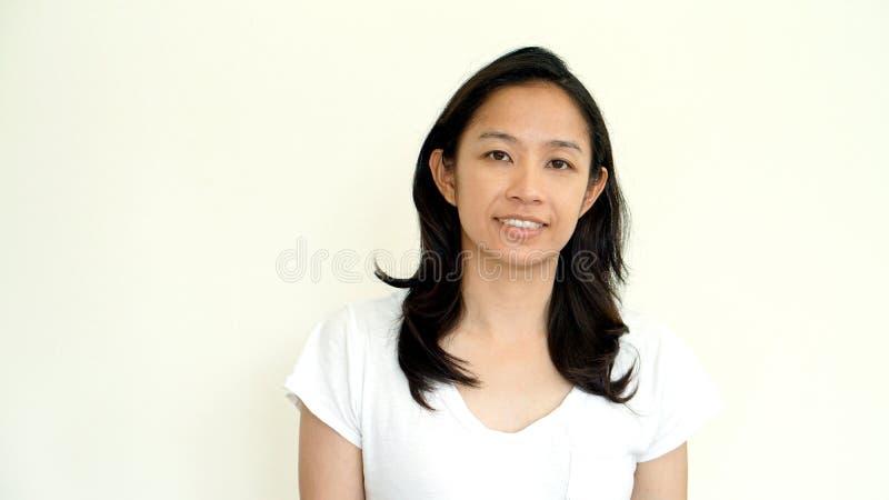 白色背景微笑的面孔的偶然亚裔女孩与放松te 免版税图库摄影