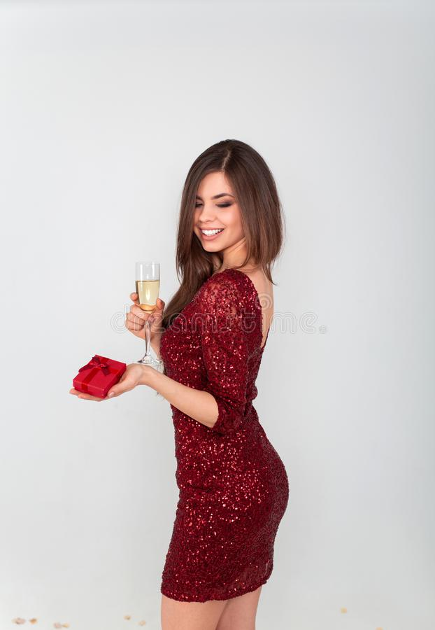 白色背景的俏丽的性感的深色的妇女 看米黄闪烁衣服饰物之小金属片的晚礼服的美丽的少女  免版税图库摄影