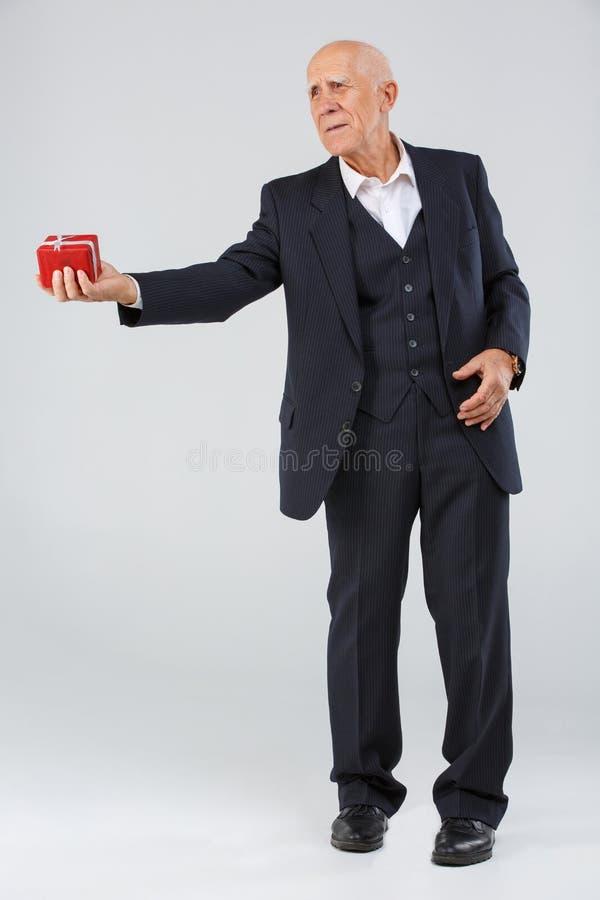 白色背景的全长年长人,在演播室,与一个礼物盒的一套黑聪明的衣服的在他的手上 库存图片