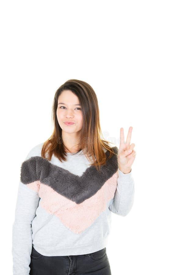 白色背景的少年女孩微笑和显示与手手指的胜利标志 库存图片