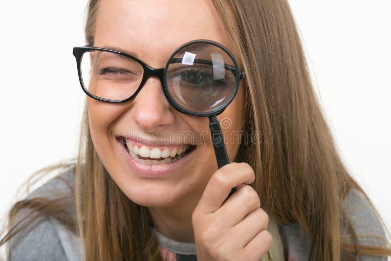 白色背景的美丽的女孩与放大镜 免版税库存图片