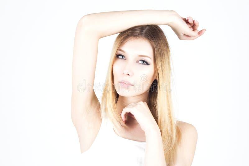 白色背景的美丽的妇女用她的被举的手 给腋窝打蜡 库存照片