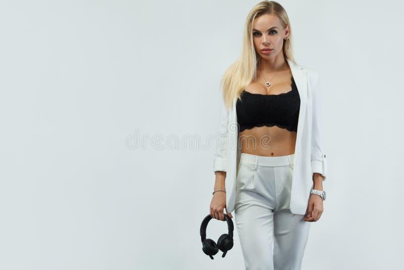 白色背景的美丽的性感的白肤金发的DJ妇女在演播室佩带的耳机 免版税库存照片