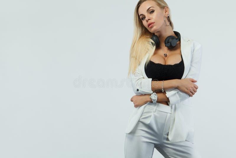 白色背景的美丽的性感的白肤金发的DJ妇女在演播室佩带的耳机 免版税图库摄影