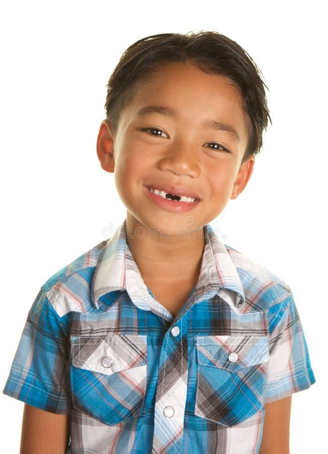白色背景的逗人喜爱的菲律宾男孩微笑与想念的前牙 免版税库存照片
