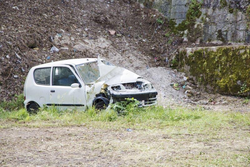 白色腐朽的汽车在一个小块围场 免版税库存照片