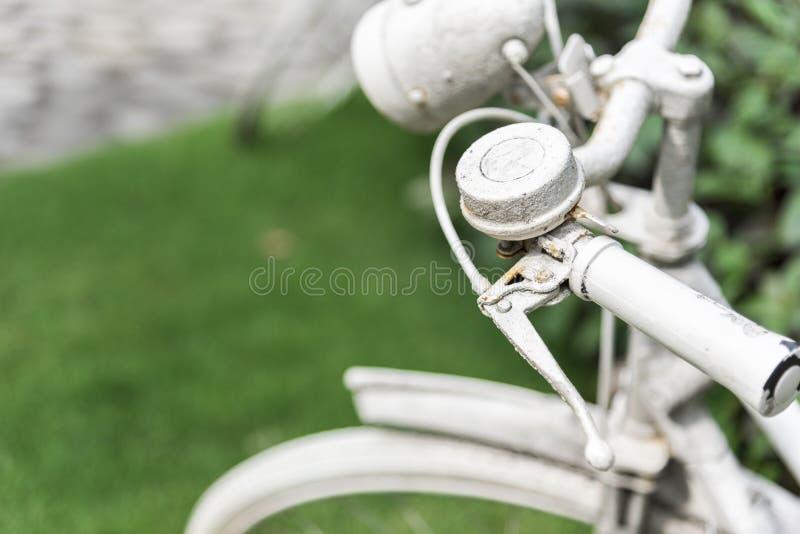 白色自行车在庭院背景中 葡萄酒和自然概念 关闭和自行车把柄 库存照片