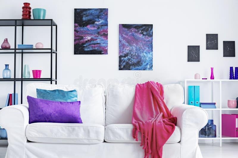 白色舒适的长沙发特写镜头有桃红色毯子和紫色和蓝色枕头的在现代客厅内部,真正的照片 免版税库存照片