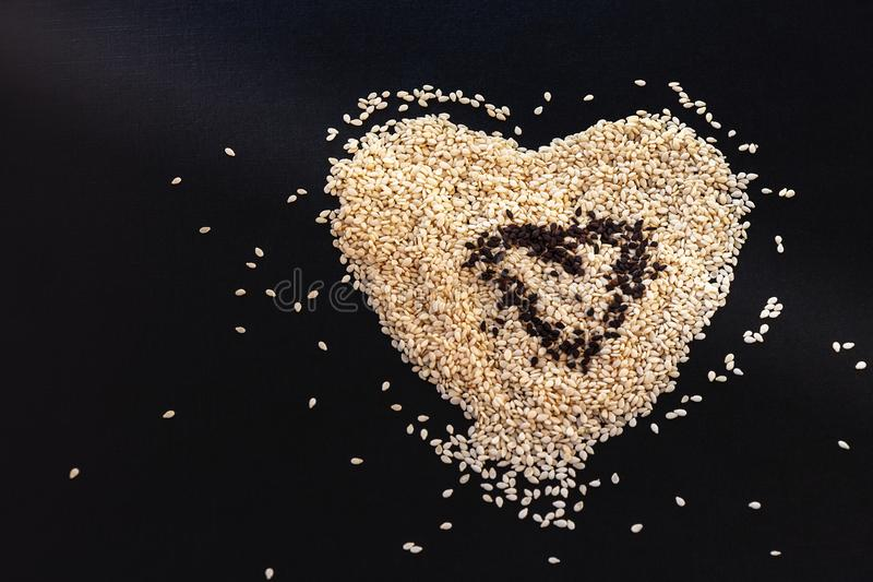 白色芝麻籽在黑背景的心脏形状安排了 库存图片