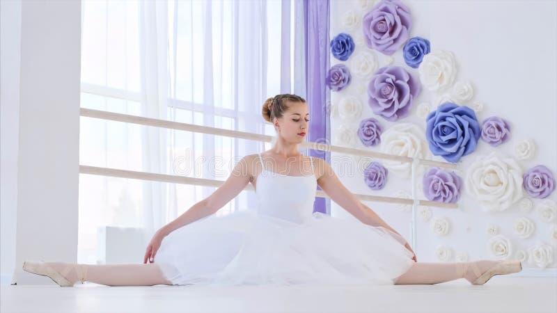 白色芭蕾舞短裙和pointes舒展的芭蕾舞女演员坐在芭蕾类的麻线 免版税库存图片