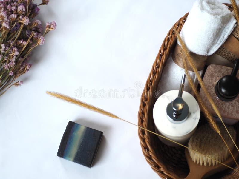 白色花饰篮中天然自制肥皂及浴具 免版税库存图片