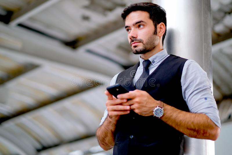 白色英俊的商人用途手机和表明乏味和哀伤的情感和立场接近杆 库存照片
