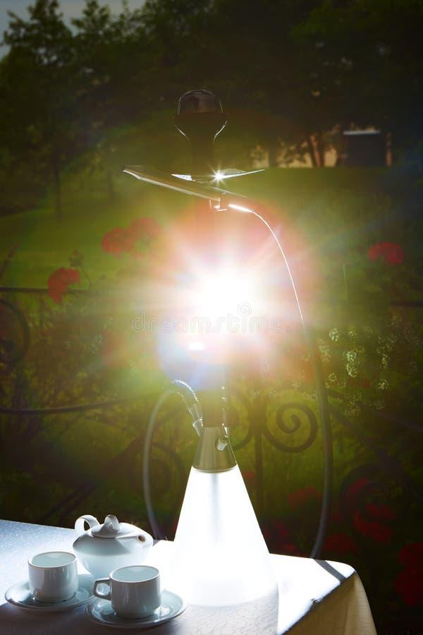 白色茶壶、两个杯子和太阳 游园会 库存图片