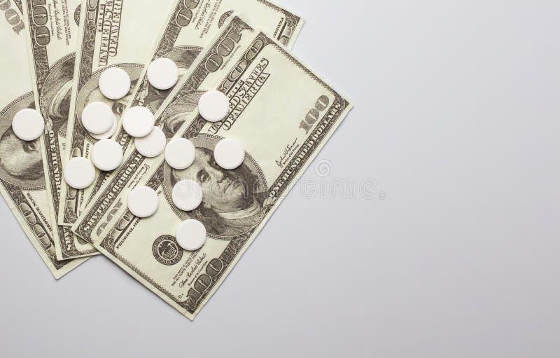 白色药片和金钱,保健费用概念,护理费用, 免版税库存照片