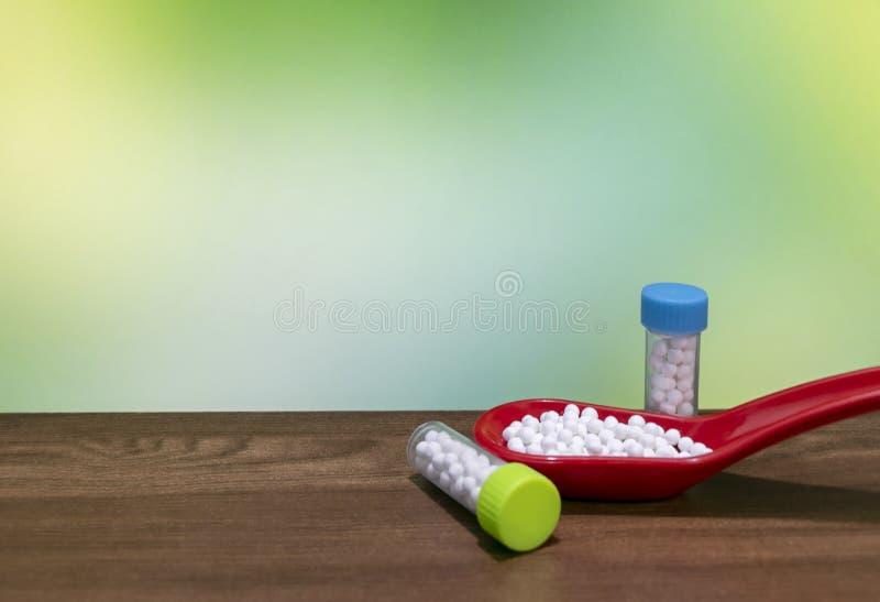 白色药片接近的看法在红色匙子的有木表面和绿色混合黄色背景上的同种疗法药物瓶的 免版税图库摄影