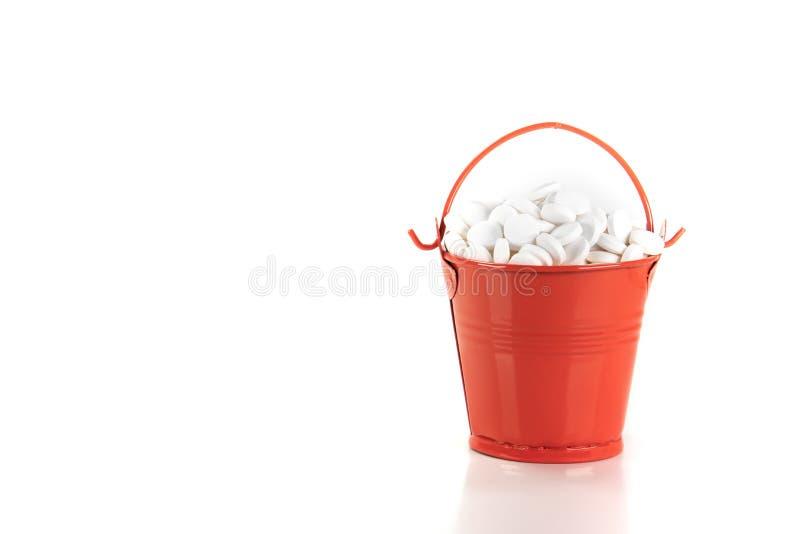 白色药片,在红色金属桶的片剂 免版税库存照片