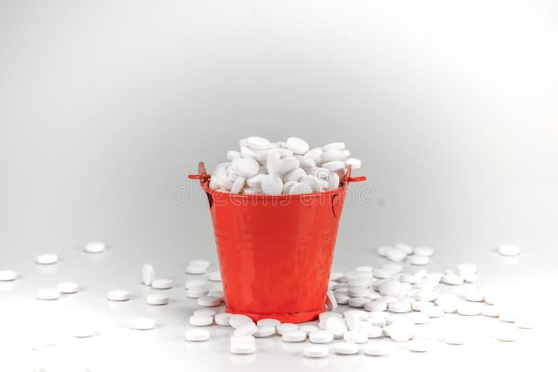 白色药片,在红色金属桶的片剂 库存图片