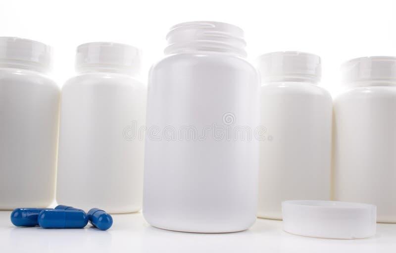 白色药瓶开放在盖帽和蓝色药片之间的柜台 库存图片