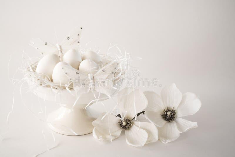 白色葡萄酒复活节场面,蛋糕立场用鸡蛋,花,反对白色背景,空间文本的 免版税库存照片