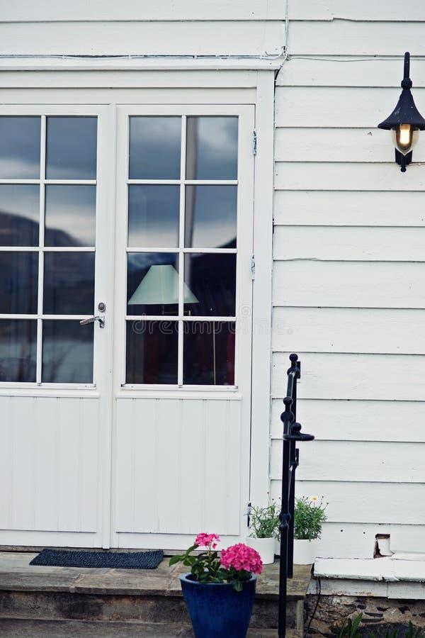 白色葡萄酒木门对白色墙壁和灯 库存照片