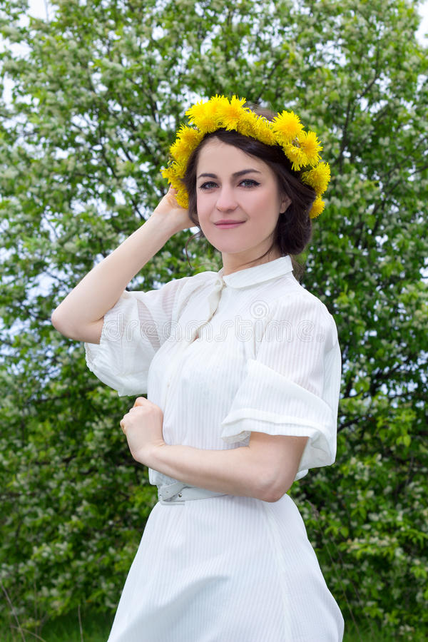白色葡萄酒礼服的美丽的妇女有在hea的花花圈的 库存照片