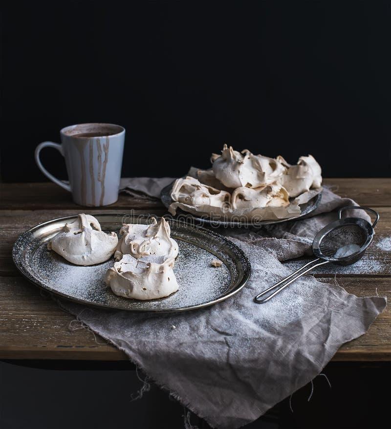 白色蛋白甜饼和杯子在一张土气木桌上的热巧克力 黑backdro 图库摄影