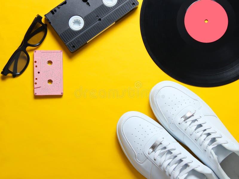 白色行家运动鞋,乙烯基板材,音频和录象带,3d在黄色背景的玻璃 减速火箭的样式 顶视图 免版税库存图片