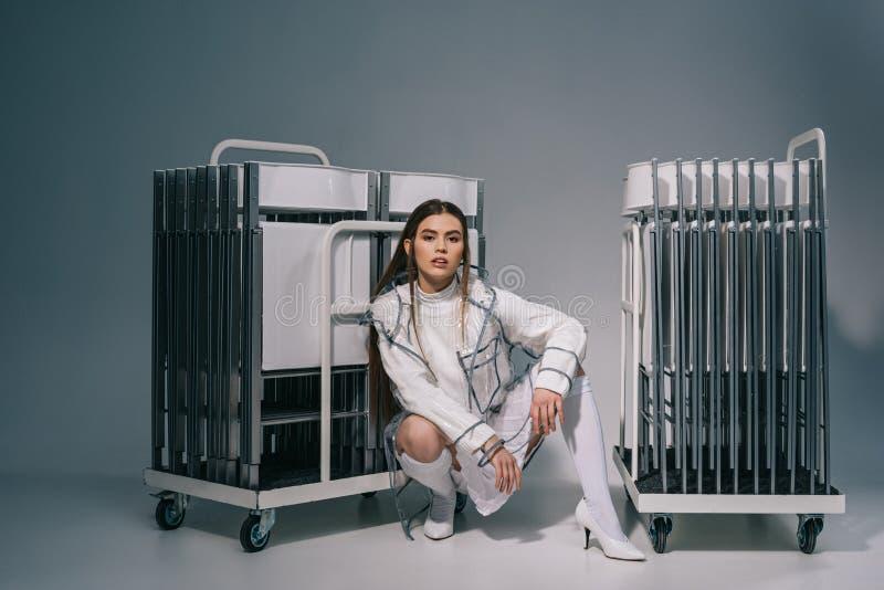 白色衣物和雨衣的时髦的妇女有在看照相机后的可折叠椅子的在灰色 库存图片