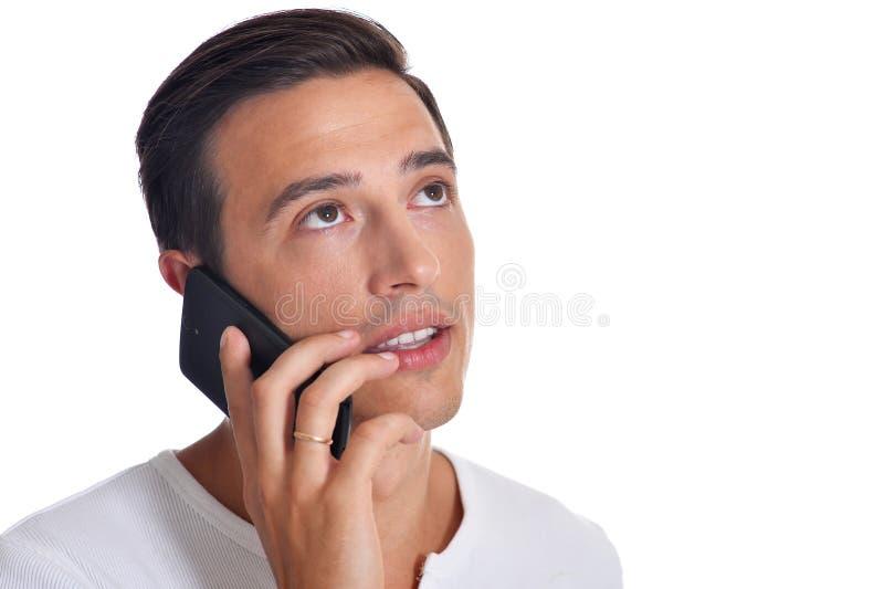 白色衣物的英俊的年轻人谈话在摆在白色背景的智能手机 免版税库存图片