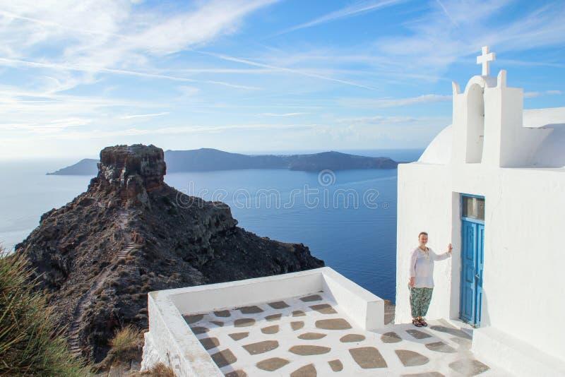 白色衣裳的一个少女游人在圣托里尼海岛上的一个白色教会旁边微笑着  爱琴海和火山在su 库存图片