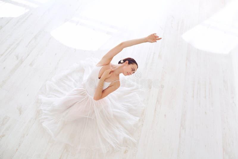 白色衣裳的一位芭蕾舞女演员在一个白色演播室 免版税库存图片