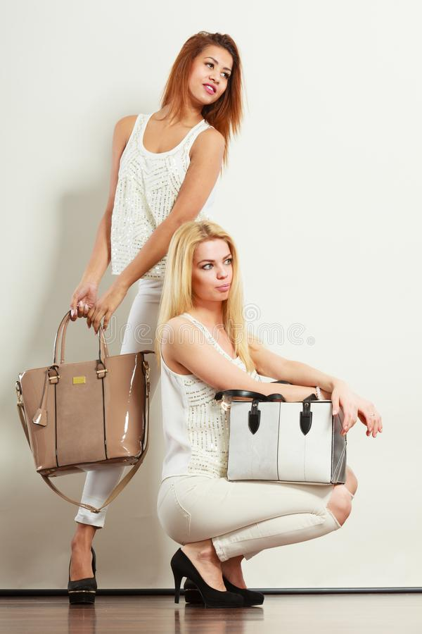 白色衣裳的两名妇女有袋子提包的 图库摄影