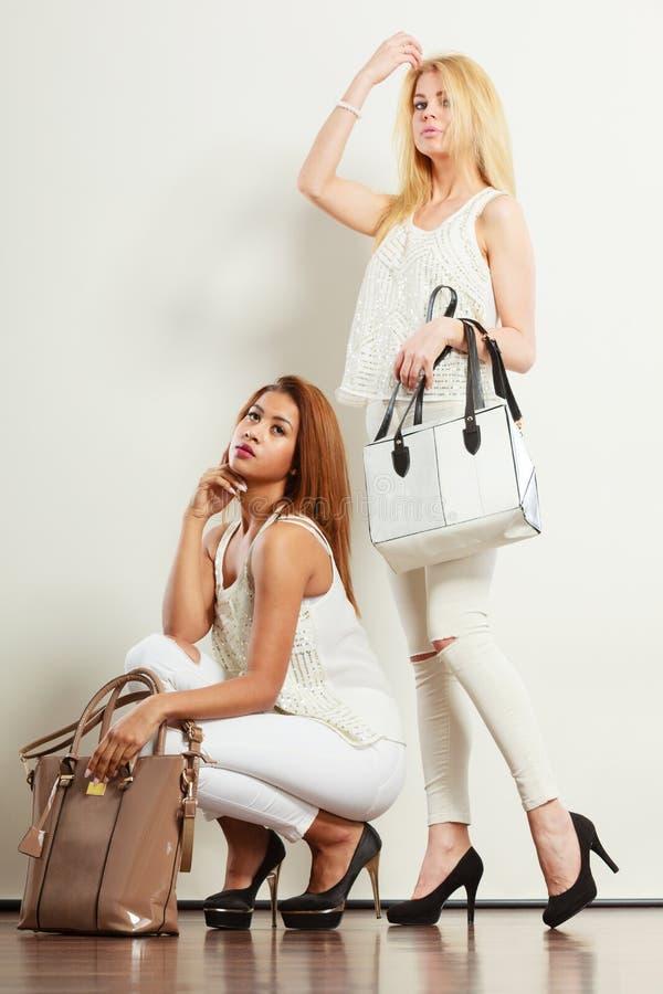 白色衣裳的两名妇女有袋子提包的 免版税库存照片