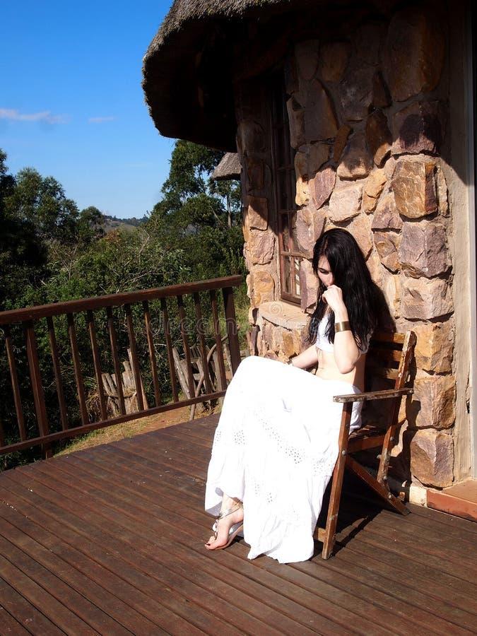 白色衣裳的体贴的女孩坐游廊 库存图片