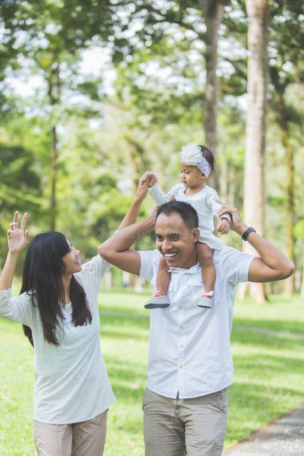 白色衣裳的父母走与他们的小女儿的 免版税图库摄影
