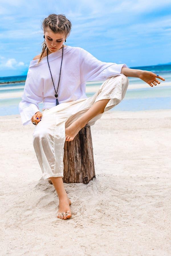 白色衣裳的美丽的时髦的年轻女人在海滩 库存图片