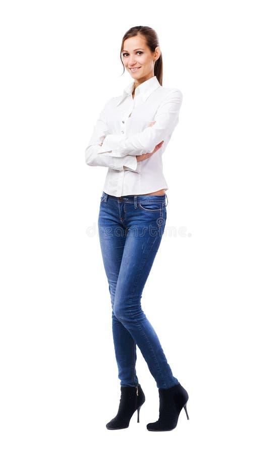 白色衬衣和蓝色牛仔裤的可爱的妇女 免版税库存图片
