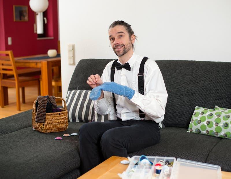 白色衬衣的人有弓领带修补工作袜子的 免版税库存图片